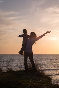 Мать с дочерью на берегу моря на фоне заката. силуэт