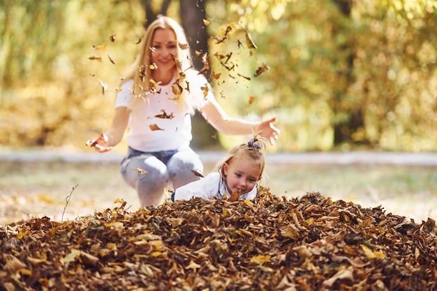 그녀의 딸과 함께 어머니는 가을 공원에서 함께 재미를 가지고 있습니다.