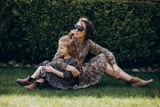 裏庭で楽しんでいる彼女の娘を持つ母