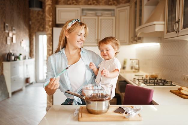 溶かしたチョコレートを混ぜる彼女の娘を持つ母