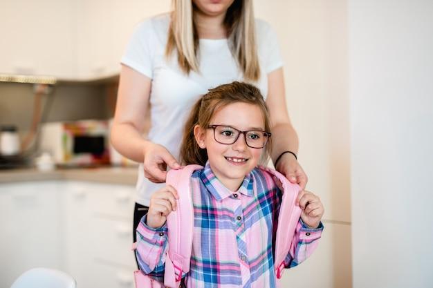 学校の準備をしている娘と一緒の母。