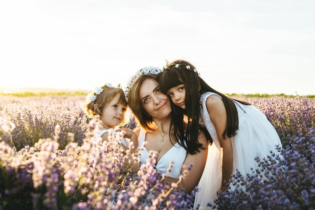 A mother with her daughters at sunset in the lavender field at sunset. concept of international women's day