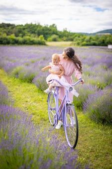 라벤더 배경 체코 공화국에 보라색 자전거에 그녀의 작은 daugher와 어머니