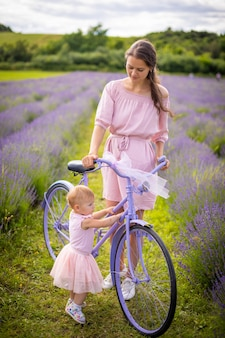 Mother with her little daugher on purple bicycle on lavender background in czech republic