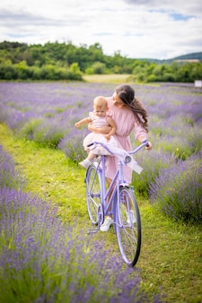 Mother with her little daugher on purple bicycle on lavender background czech republic