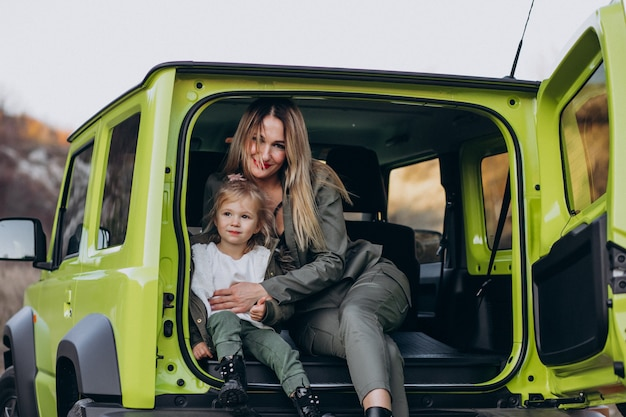 Mother with her little daugher sitting in the back of the car
