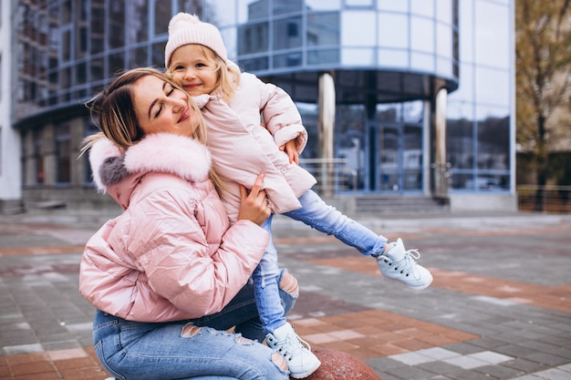 Mother with her little daughter dressed in warm cloth aoutside the street