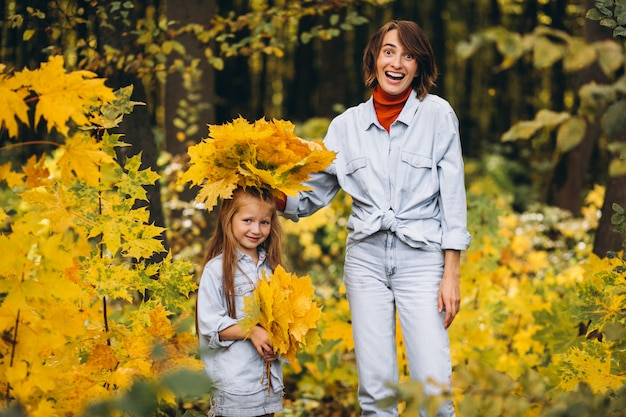 Mother with her little daughter in forest full of golden leaves