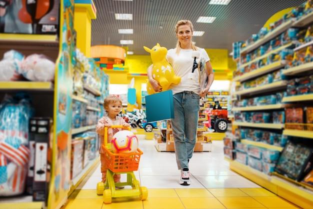 キッズストアでたくさんのおもちゃを買う彼女の小さな女の子の母。