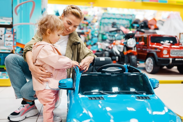 キッズストアで電気自動車を選択する彼女の小さな女の子の母。