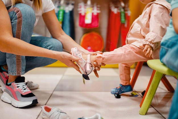 Мать с ее маленькой девочкой, выбирая обувь в детском магазине.