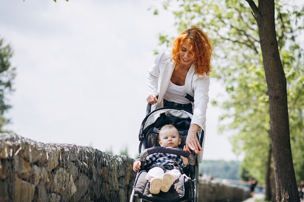 Mother with her little son in a baby carriage in park