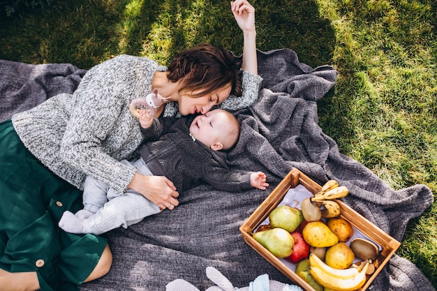 Mother with her little son having picnic on a back yard