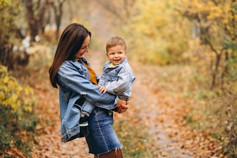 Mother with her little son in autumn park