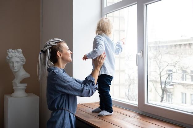창 밖을보고 그녀의 작은 아들과 어머니