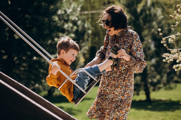 Мать с маленьким сыном качается на заднем дворе
