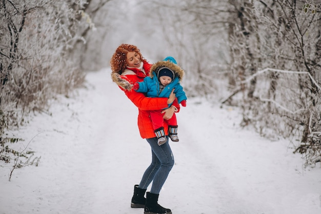 Mother with her little son together in a winter park