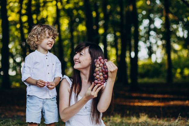 Madre con suo figlio che ha picnic nella foresta