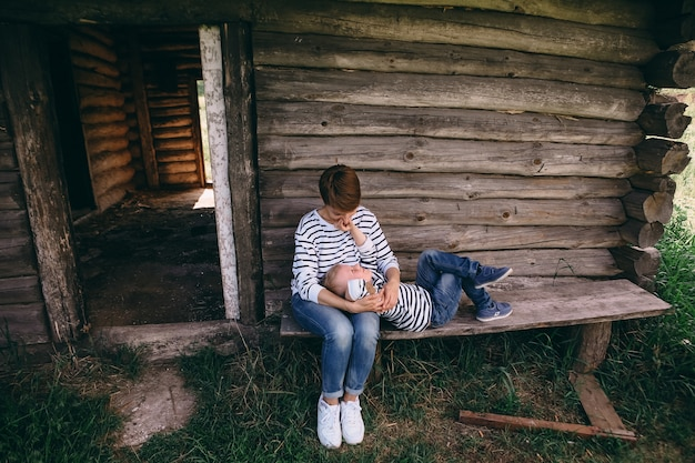 Mother with her son in her arms near old wooden house, lifestyle