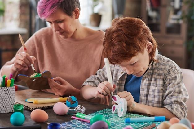 Мать с сыном сидят за столом и рисуют фигуры красками во время занятий по искусству