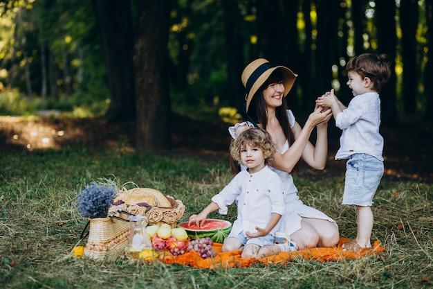Madre con i suoi figli che hanno picnic nella foresta