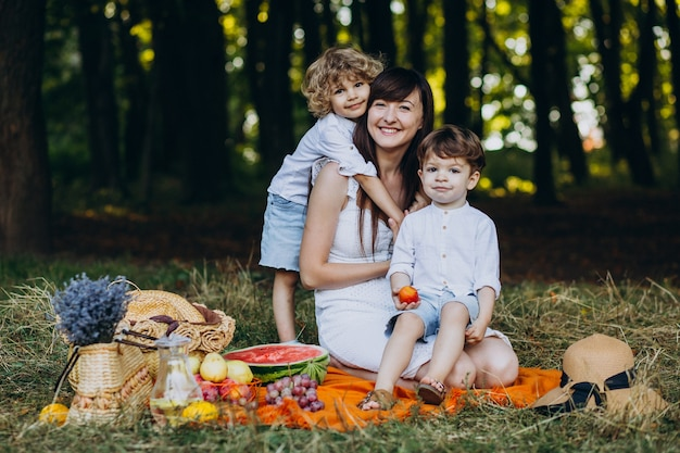 森でピクニックをしている彼女の息子を持つ母
