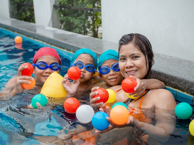 Mother with her sons playing with balls in the pool
