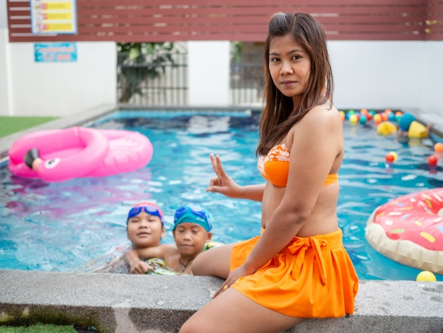 Mother with her sons in the pool