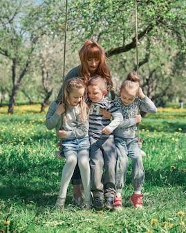 Мать с тремя детьми в саду качелей. концепция совместного отдыха