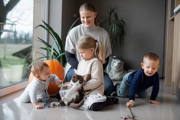 집에서 바닥에 고양이와 노는 그녀의 세 자녀와 어머니 프리미엄 사진