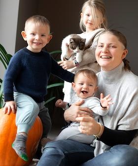 집에서 바닥에 고양이와 노는 그녀의 세 자녀와 어머니