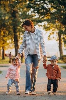 가을 공원에서 그녀의 유아 아들과 딸과 함께 어머니