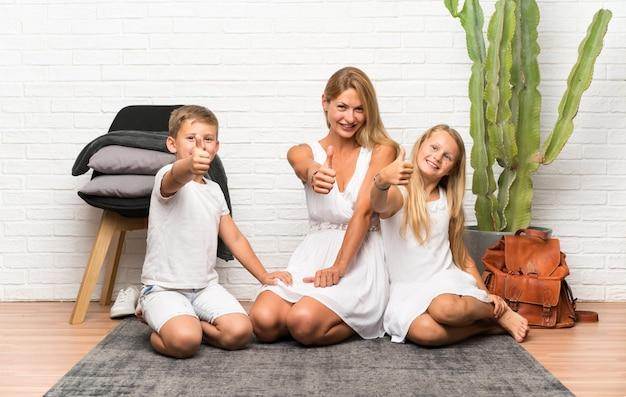 엄지 손가락으로 실내에서 그녀의 두 아이와 어머니