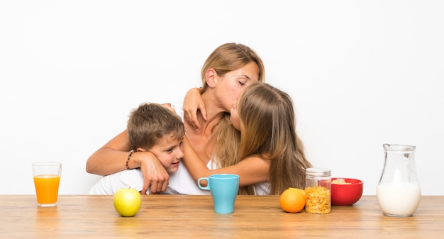 Mother with her two children having breakfast and hugging