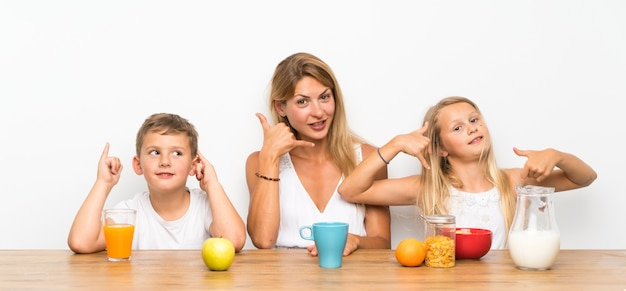 Mother with her two children having breakfast and  making phone gesture