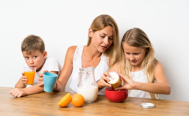 Mother with her two children having breakfast