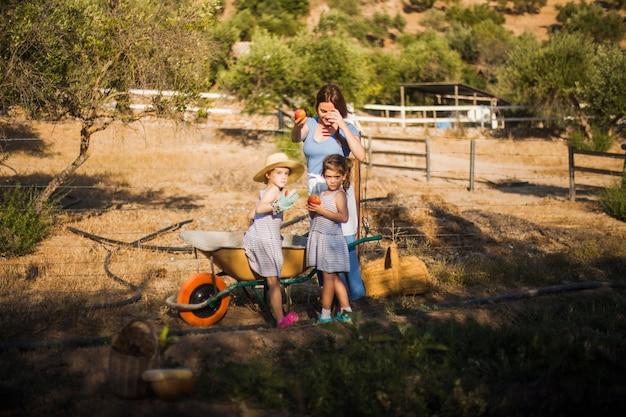 Мать с двумя ее дочерью с красным зрелым яблоком в поле