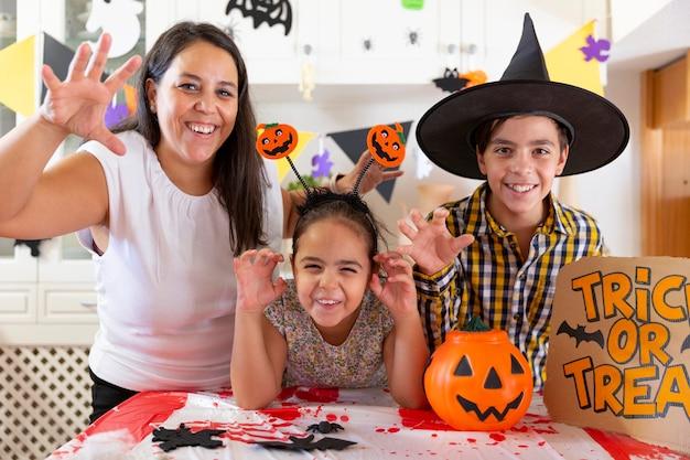 ハロウィーンパーティーを祝っている間、おかしなポーズをとっている2人の子供を持つ母親。ひとり親家庭のコンセプト。