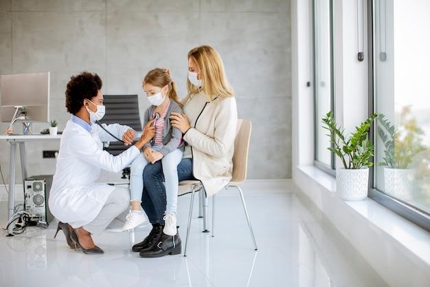 Мать с маленькой дочерью на осмотре педиатра у афро-американской женщины-врача