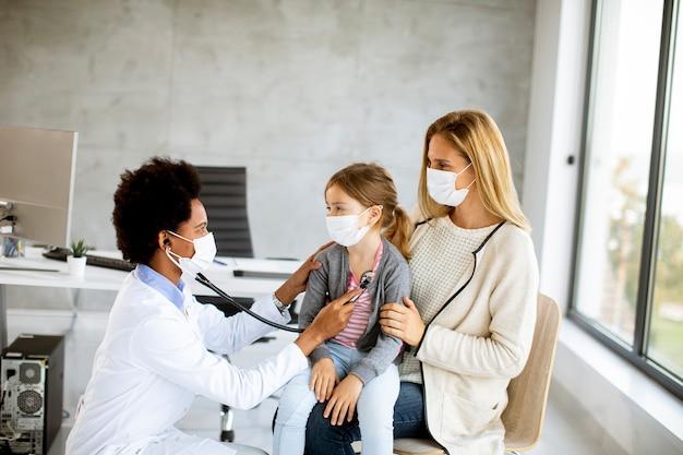 アフリカ系アメリカ人の女性医師による小児科医の検査で彼の幼い娘と母親