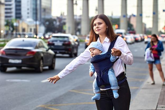 Мать с ребенком в слинге останавливает такси на улице с движением в дневное время.