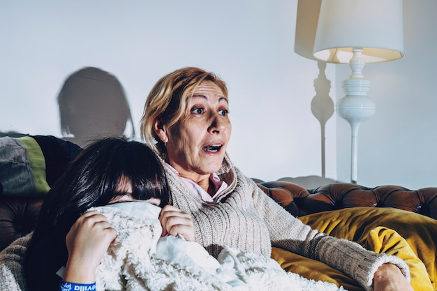 Mother with kid watching interesting movie