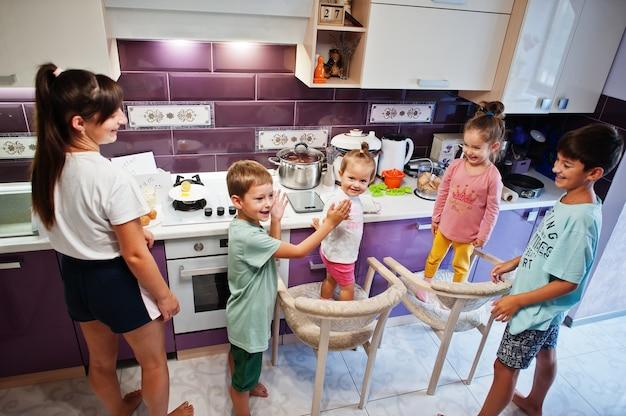 キッチンで料理をしている子供を持つ母親、幸せな子供の瞬間。お互いにハイタッチをします。