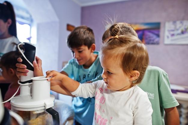 キッチンで料理をしている子供を持つ母親、幸せな子供の瞬間。ブレンダーで作業します。