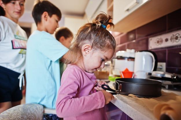 キッチンで料理をしている子供を持つ母親、幸せな子供の瞬間。