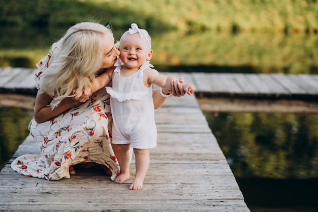 湖のほとりに小さな赤ん坊の娘を持つ母