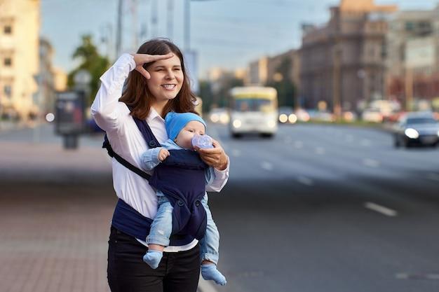 Мать с маленьким мальчиком в слинге стоит возле движения на улице
