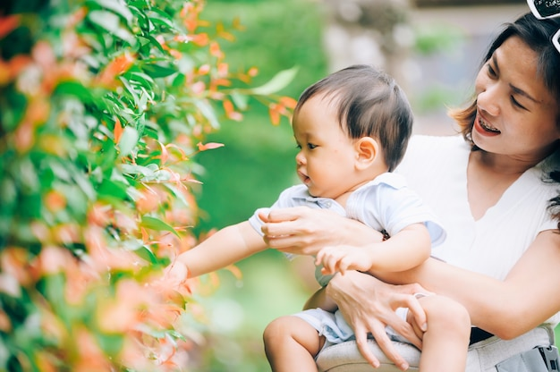 Mother with little child in white blooming garden. woman with son in green leaves,happy family outdoors in spring