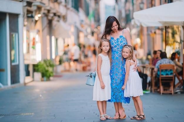 Мама с маленькими милыми дочерьми едят мороженое на улице