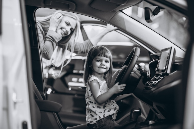 Mother with little daughet sitting in a car in a car showroom